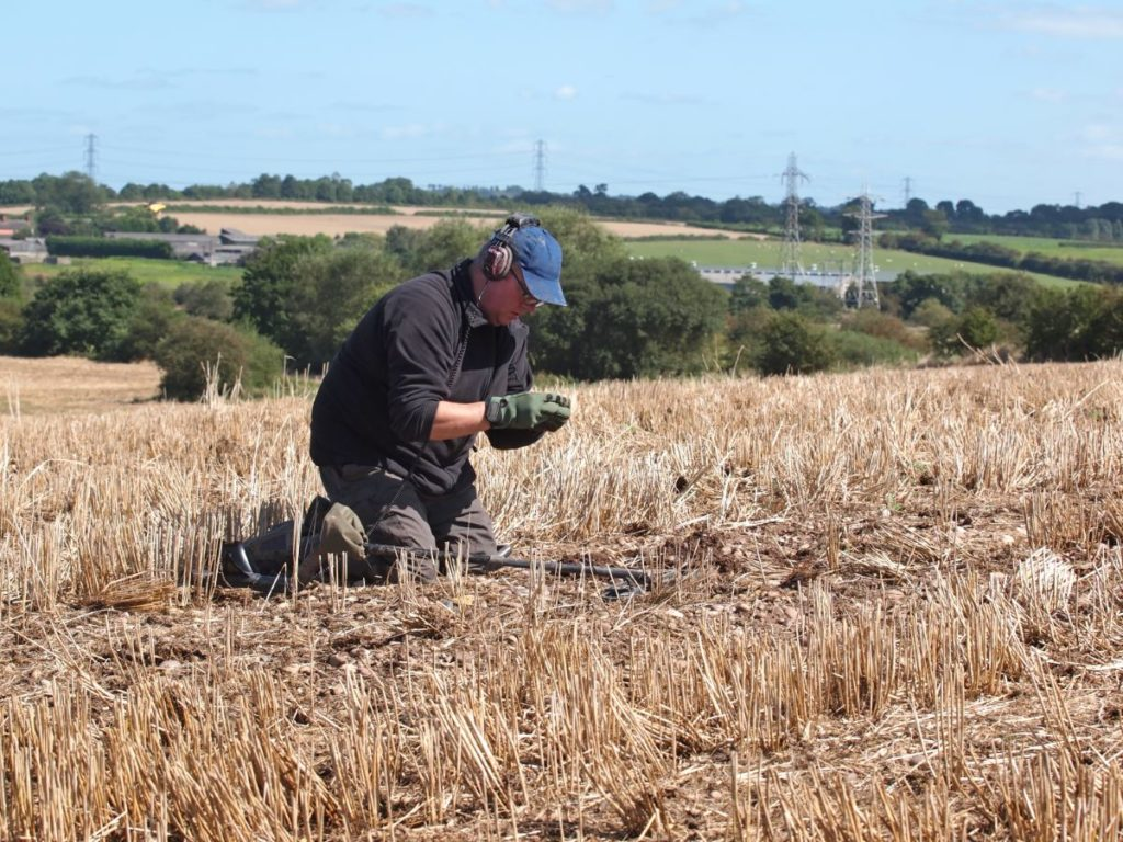 Man metal detecting on his knees and looking at a find