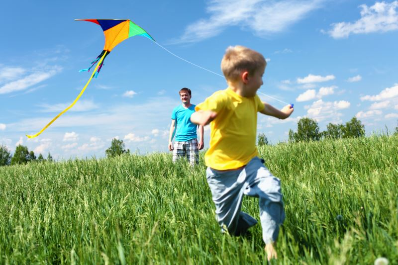 Kid flying a kite on a sunny day while his dad looks on in the background